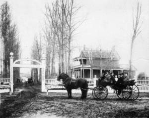 Home of Mr. Addison Nathan Baker on Grand Avenue (West Colfax Avenue) in Denver, Colorado. The farm house is a two story brick structure surrounded by a fence with a gate. The Baker family, men, women, and children, sit in a horse drawn carriage.