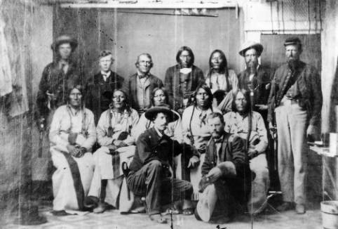 Standing L-R: Unidentified, Dexter Colley (son of Agent Samuel Colley), John S. Smith,  Heap of Buffalo, Bosse, Sheriff Amos Steck, Unidentified soldier. Seated L-R: White Antelope, Bull Bear, Black Kettle, Neva, Na-ta-Nee (Knock Knee). Kneeling L-R: Major Edward W. Wynkoop, Captain Silas Soule.