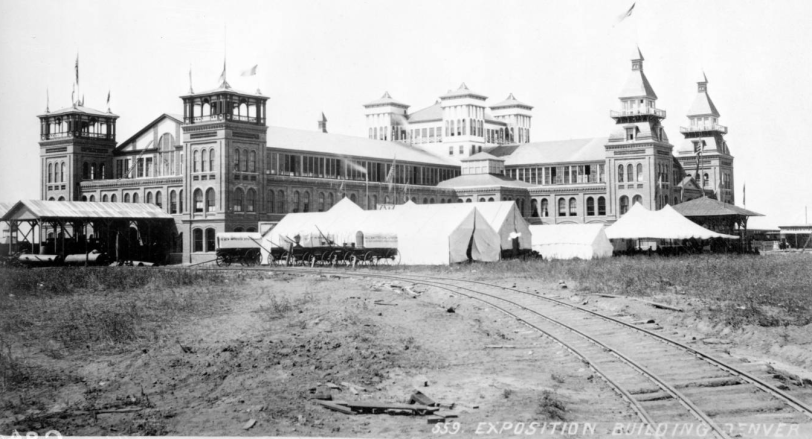 National Mining and Industrial Exposition building. The National Mining and Industrial Exposition opened August 1, 1882 at the corner of South Broadway and Exposition Avenue in Denver, Colorado, exhibiting mining and industrial equipment and resources. The buildings were removed after the third annual exhibition in October, 1884. Long, white tents and covered wagons stand in front of the complex near a railroad track. [1882?]  Courtesy DPL Western History Collection C-94