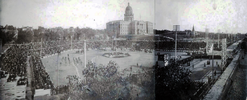 People crowd bleachers in an arena, probably for the Festival of Mountain and Plain, at the corner of Colfax and Broadway Streets, in Denver, Colorado; a marching band and horses are in the arena. The Colorado State Capitol building is in the distance. [between 1890 and 1910?] Courtesy DPL Western History Collection Z-6110