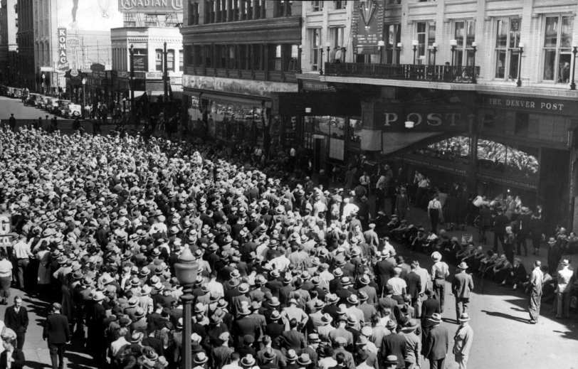 "Whatta Game! People crowd Champa Street by the Denver Post newspaper headquarters in downtown Denver, Colorado, to listen to a baseball game. An electric scoreboard is above storefronts on a balcony on the Denver Post building; canopy reads: ""Post."" Business signs read: ""Komac"" and ""Canadian Club."" Title from newspaper clipping attached to back of photoprint; also reads: ""Just a portion of the huge crowd that gathered in front of The Post Wednesday and thrilled, pitch by pitch, to the Cub's victory over the Tigers in the opening game of the World Series. Thursday, and all remaining days of the series, these games will be played for you on The Post scoreboard."" 1935 October 3. Courtesy DPL Western History CollectionX-28817"