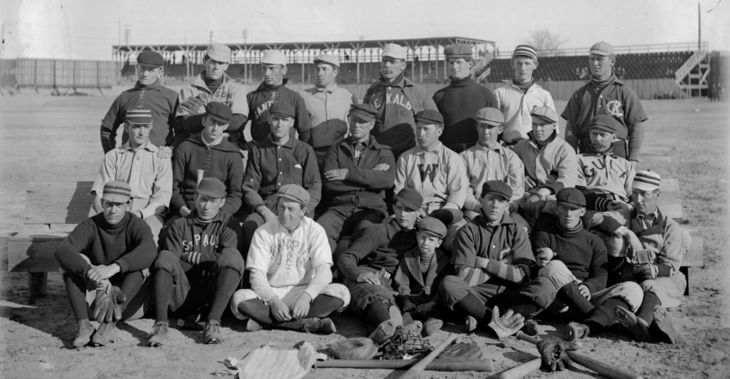 "Members of the Denver Bears baseball team pose outdoors at a baseball field in Denver, Colorado. They are identified as: standing: Len ""Dad"" Shirk, Walter Price (P) Walter Bissell, unknown, ""Old Hoss"" Hausen (C), Happy ""Klondike"" Kane (P), J. H. Vizard (OF), Jack Holland (INF & OF). Middle: Pop Eyler (P), Dakin ""Dusty"" Miller (OF), Tom ""Tacks"" Parrott (P, OF, INF), Charley Kight (P) Charles ""Princeton Charlie"" Reilly (3B), Charlie Zeitz (OF), W. E. ""Bill"" Hickey (INF), Al Hickey (C). Front: Mons ""Eddie"" Webster (P), Walter ""Wizard"" Preston (CF), Jack Sullivan, Pearl ""Casey"" Barnes (INF), Clarence Leisenring, Mascot, Joe Tinker (2B), and W. E. Hurry McNeeley (P & INF). Courtesy History Colorado Collection CHS-B1427"