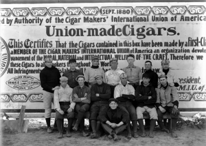 Members of the Denver Bears baseball team pose outdoors at a baseball field in Denver, Colorado. Some of the men wear uniforms. A cigar union sign is used as the backdrop. Courtesy History Colorado Collection CHS-B1369
