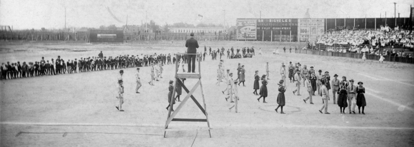 "Broadway Park II. Men and women perform an exercise demonstration at the athletic field in Broadway Park, West 6th (Sixth) Avenue and Broadway in Denver, Colorado. A man stands on a wooden elevated platform and oversees the athletes. The women, in bloomers, hold Indian clubs, and march with men in suits, ties and cowboy hats who carry exercise sticks. Men and women stand near the field or sit on a fence or on bleachers. Painted signs read: ""Dr. Bicycles Athletic Goods, fully guaranteed"" ""Earle, a good throw throws it right"" and ""Attention batsmen, hit this sign and get 100 US 5 [cents] Ci[gars]."" [between 1900 and 1920?] Courtesy DPL Western History Collection Z-2725"