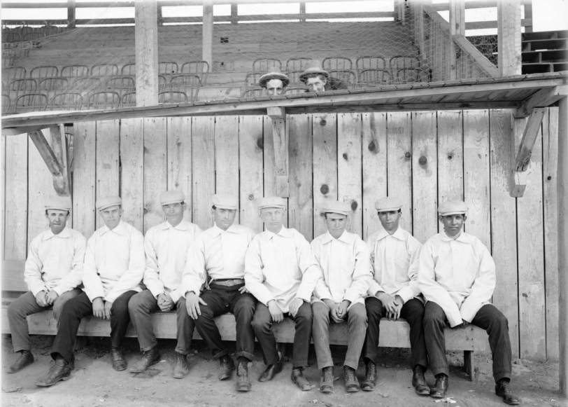 "Members of the Denver Bears baseball team pose in a dugout in Broadway Park at 6th (Sixth) Avenue and Broadway in Denver, Colorado. They are identified as (left to right): Earnest ""Kid"" Mohler (2B), W. A. ""Bill"" Hickey (IF & OF), Jack Holland (IF & OF), Joe Tinker (IF), Eddie ""Kid"" Lewee (SS), Charlie Zeitz (OF), Henry Schmidt (P), and unknown. [1900] Courtesy History Colorado Collection CHS-B1456"